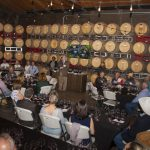 Image of people gathered around wine barrels