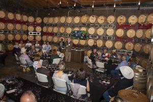 Image of people gathered around wine barrels