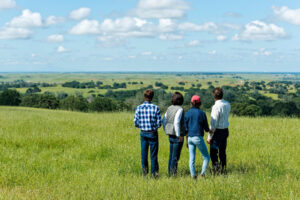Image of family of four gazing out over green pasture.