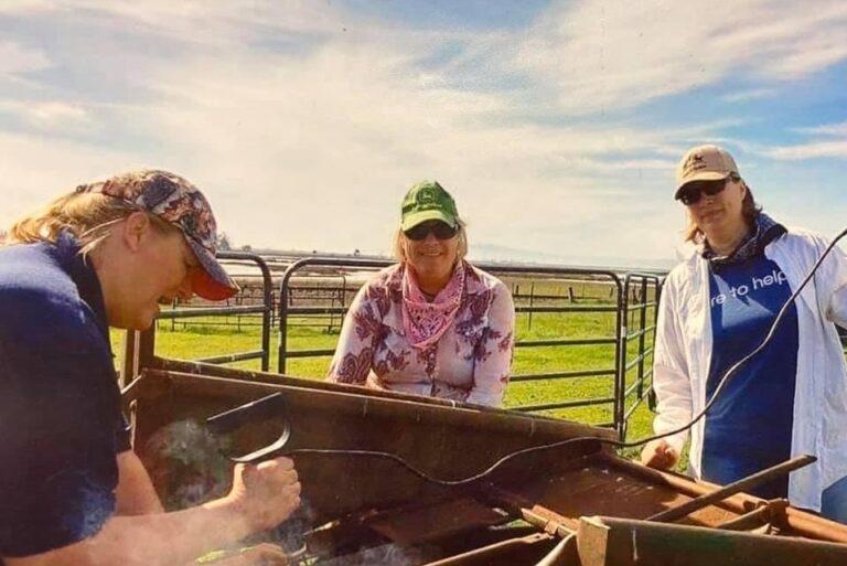 Image of three women branding cattle