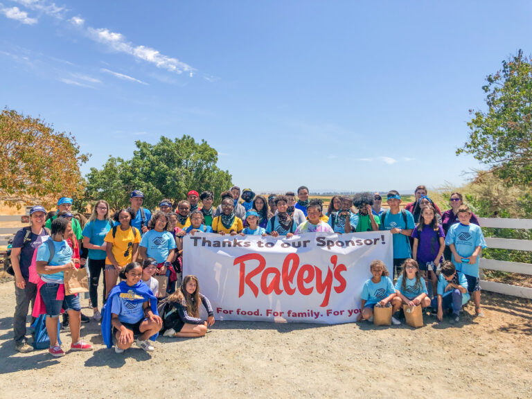 Kids gathered around sign with Raley's logo
